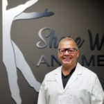 Dr. Gunn shown standing in front of Shore Wellness Med Spa Sign in office